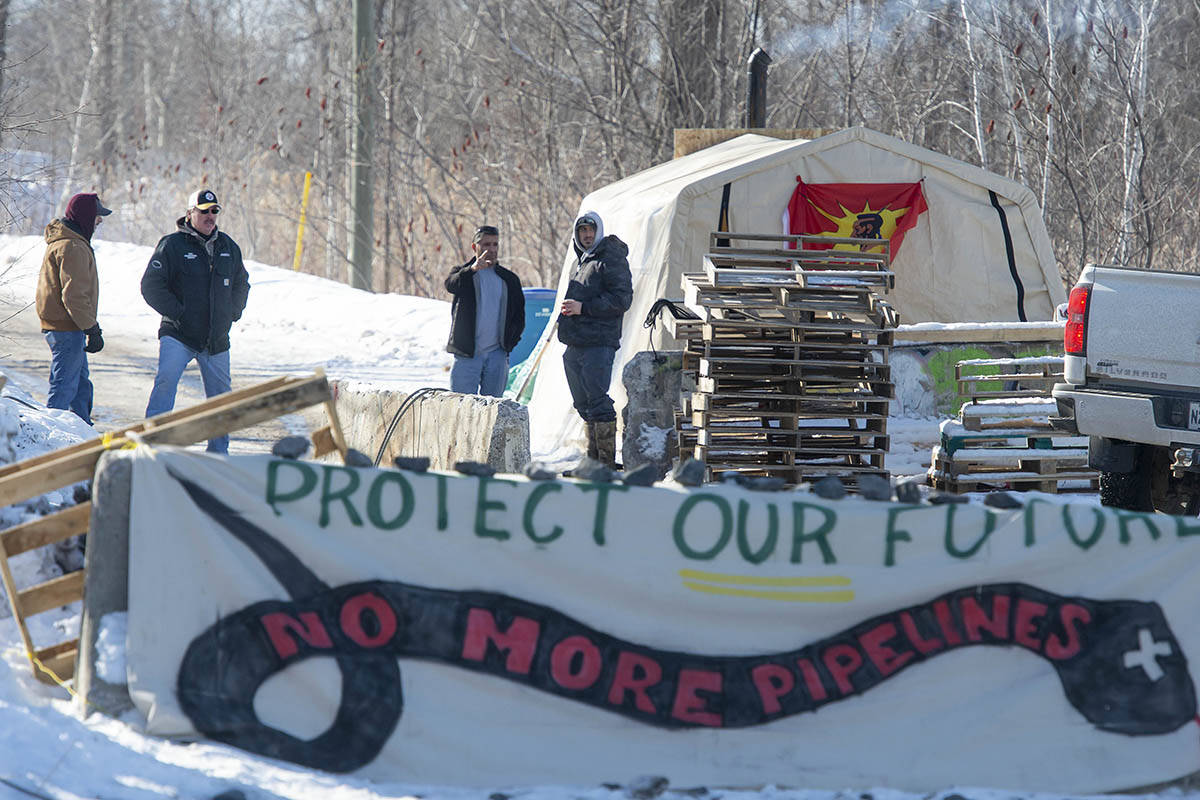 FILE – Residents of the Kahnawake Mohawk Territory southwest of Montreal continue to monitor a blockade leading to blocked railroad tracks that pass through their community as they protest in support of Wet'suwet'en hereditary chiefs on Sunday, March 1, 2020. THE CANADIAN PRESS/Peter McCabe