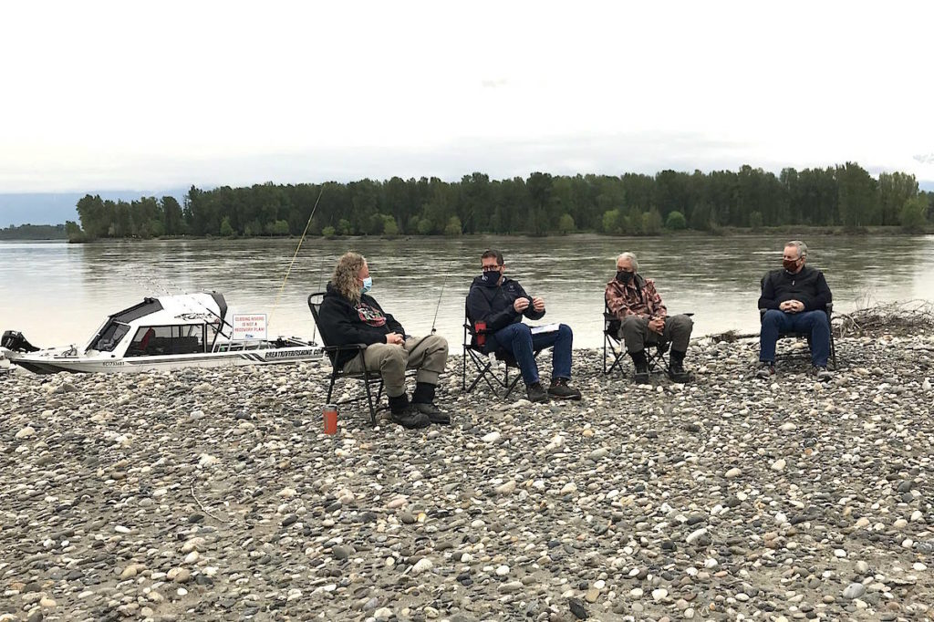 Dean Werk of FV Salmon Society, Prince George-Peace River-Northern Rockies MP Bob Zimmer, Fred Helmer of FRSA, and Abbotsford MP Ed Fast discuss fisheries on a gravel bar in the Fraser River near Chilliwack on April 28, 2021. (Jennifer Feinberg/ Chilliwack Progress)