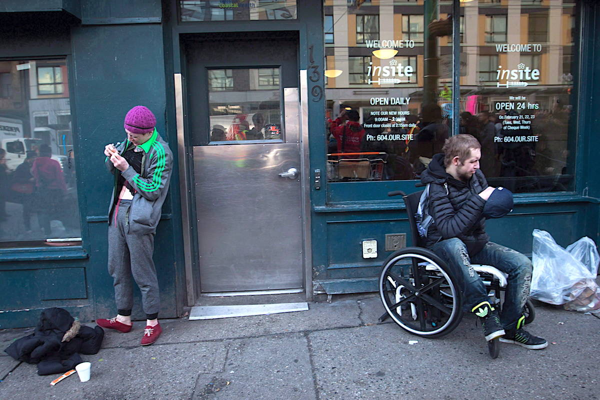 A woman, left, prepares to inject herself with an unknown substance as a man sits in a wheelchair outside Insite, the supervised consumption site, in the Downtown Eastside of Vancouver on February 21, 2017. THE CANADIAN PRESS/Darryl Dyck