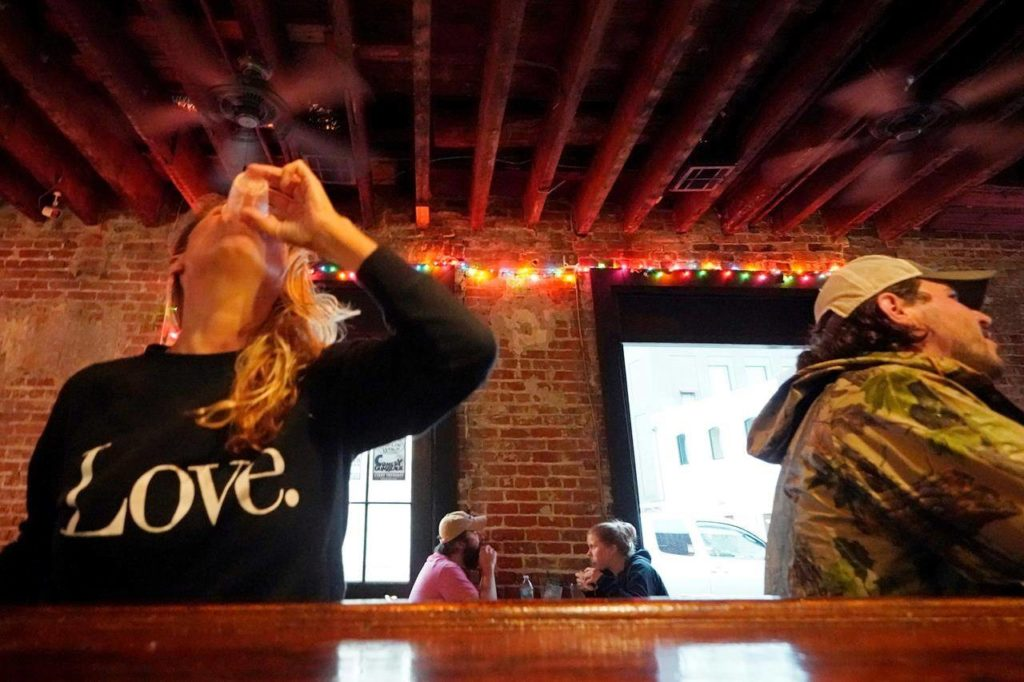 Allison Richter drinks her free shot at the bar after receiving the Moderna COVID-19 vaccine during a vaccine event at The Howling Wolf, a music venue and bar in New Orleans. (AP/Gerald Herbert)