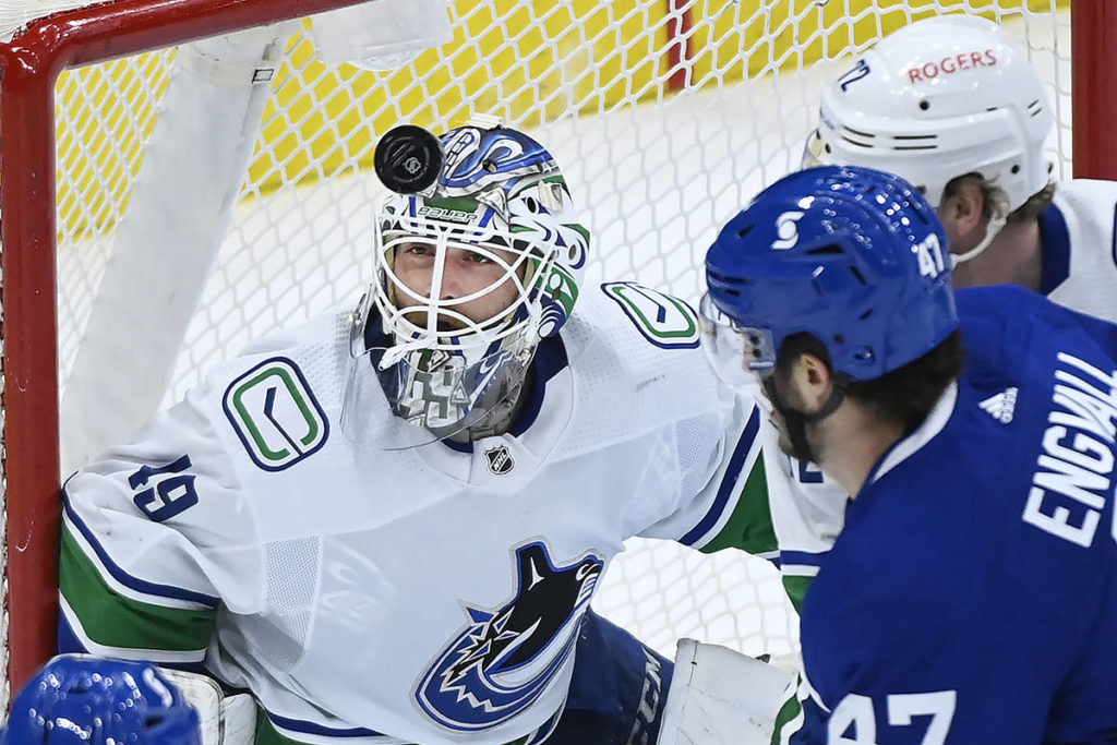 Vancouver Canucks goaltender Braden Holtby (49) eyes the loose puck against Toronto Maple Leafs forward Pierre Engvall (47) during first period NHL hockey action in Toronto on Thursday, April 29, 2021. THE CANADIAN PRESS/Nathan Denette