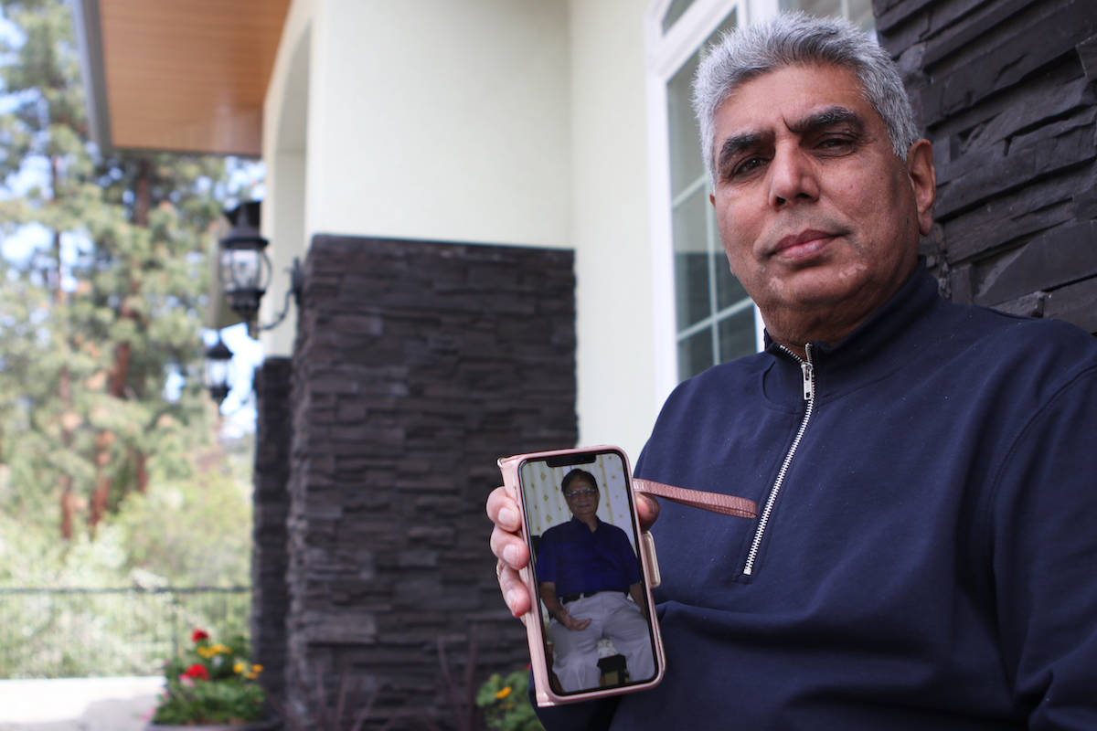Ashok Mohan holds up a photo of his brother-in-law, Vijay Sharma, who died from complications due to COVID-19 on April 27, 2021. A 72-year-old retired bank manager, Sharma had been living in the city of Jabalpur, India when he was infected and died within 10 days of contracting the virus. (Aaron Hemens/Capital News)