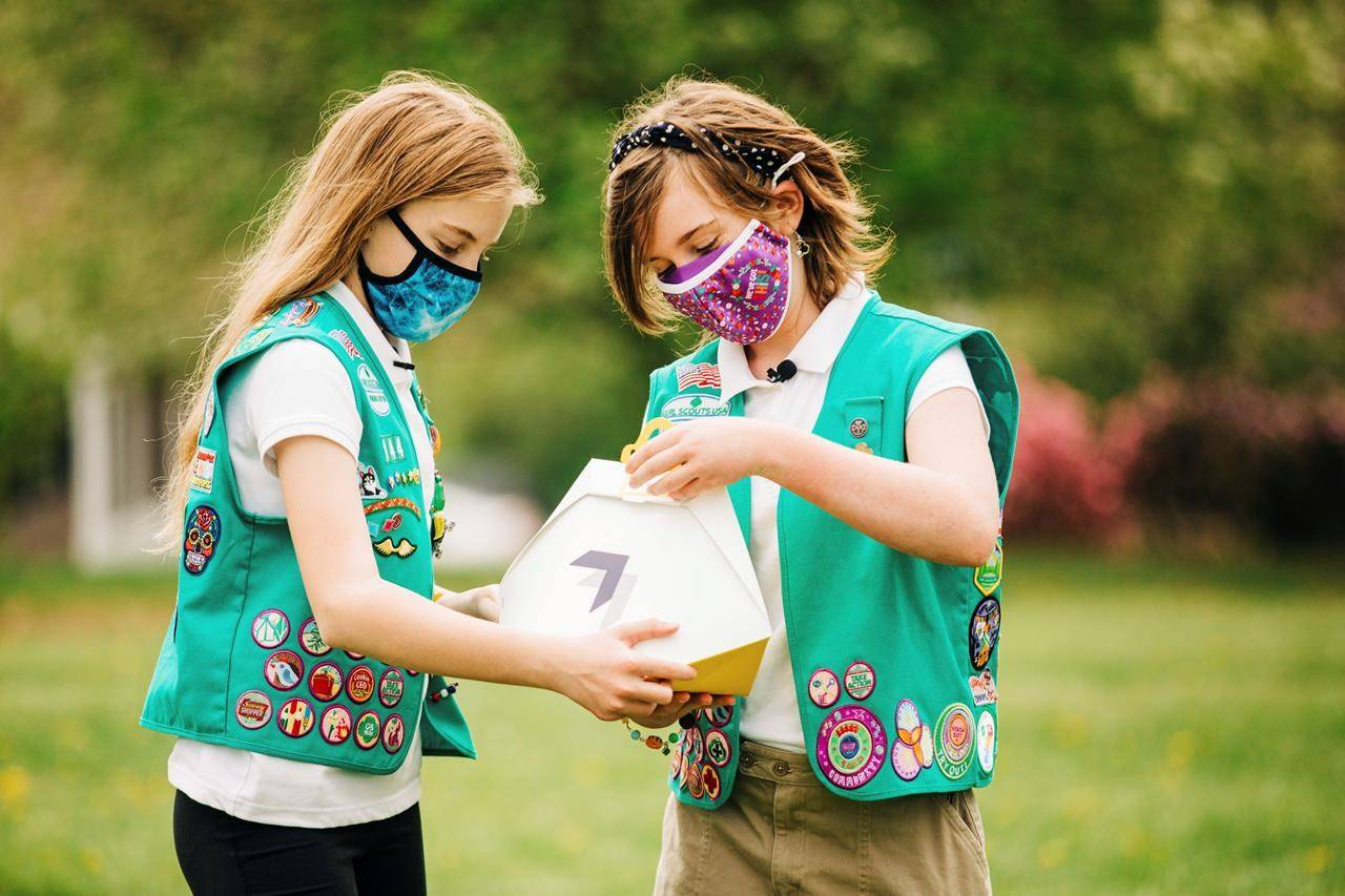 In this April 14, 2021 image provided by Wing LLC., Girl Scouts Alice Goerlich, left, and Gracie Walker pose with a Wing delivery drone container in Christiansburg, Va. The company is testing drone delivery of Girl Scout cookies in the area. (Sam Dean/ Wing LLC. via AP)