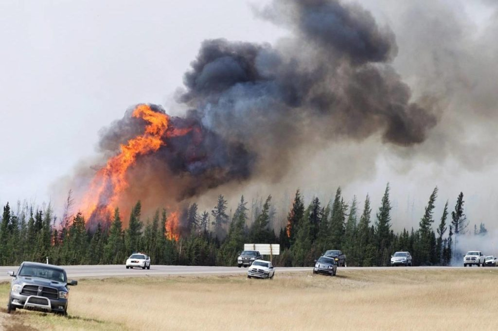 RCMP escort evacuees from Fort McMurray, Alberta past wildfires that are still burning out of control Saturday, May 7, 2016. Almost five years after a massive wildfire forced the evacuation of Fort McMurray, Alta., the northeastern Alberta oilsands hub is in another state of emergency. THE CANADIAN PRESS/Ryan Remiorz