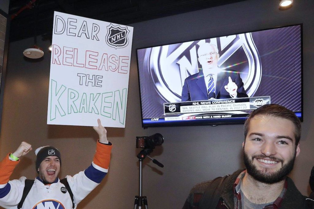 """Max Rubin cheers and holds a sign in favor of the team name """"Kraken"""" following the announcement of a new NHL hockey team in Seattle. (AP Photo/Elaine Thompson)"""