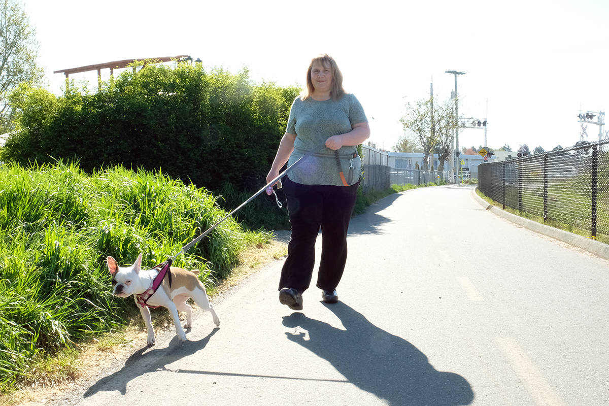 Tina Starkey with her seven-month-old puppy Sugar on the E&N Trail in Esquimalt. Starkey now carries a small personal alarm device, her thumb on the button. (Zoe Ducklow/News Staff)