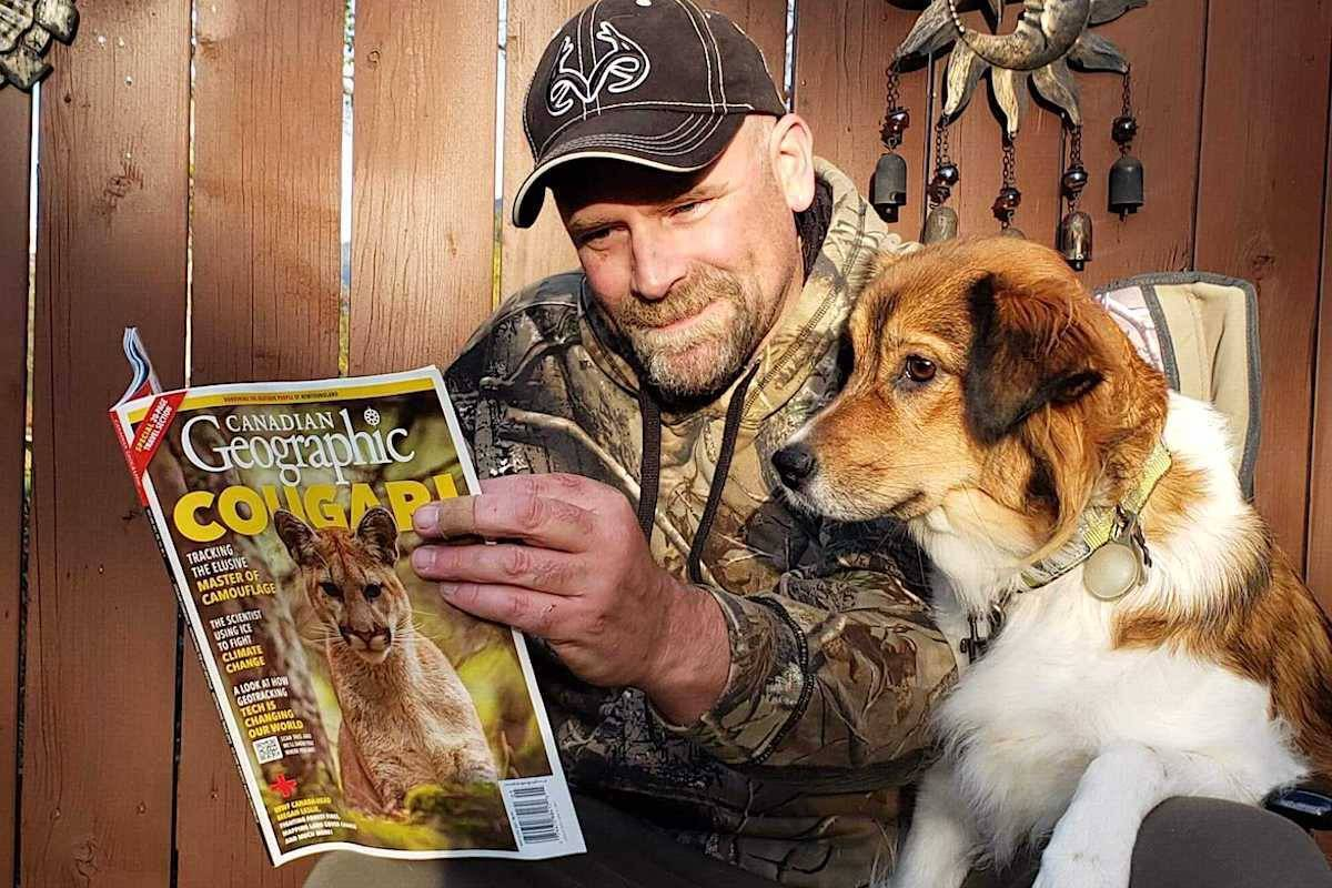Michael Handley and his field assistant Alice take a look at the new issue of Canadian Geographic. Handley's picture of a cougar won a reader vote to be on the cover. Photo: Submitted