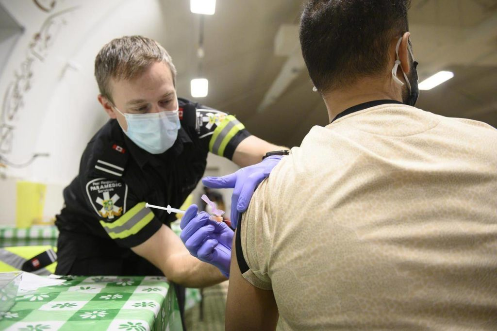 Peel Region Paramedic Ryan Kingsborough, administers a dose of the Moderna COVID-19 vaccine during a pop up clinic at the Muslim Neighbour Nexus Mosque, in Mississauga, Ont., Thursday, April 29, 2021. High vaccination rates among seniors and more infectious variants of COVID-19 are shifting the weight of pandemic in Canada towards younger people. THE CANADIAN PRESS/Christopher Katsarov
