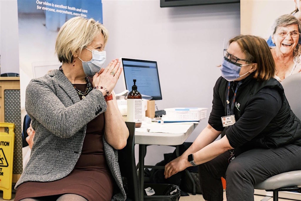 Provincial health officer Dr. Bonnie Henry thanks an Island Health nurse after joining staff for the first round of COVID-19 vaccine, Victoria, Dec. 22, 2020. (B.C. government)