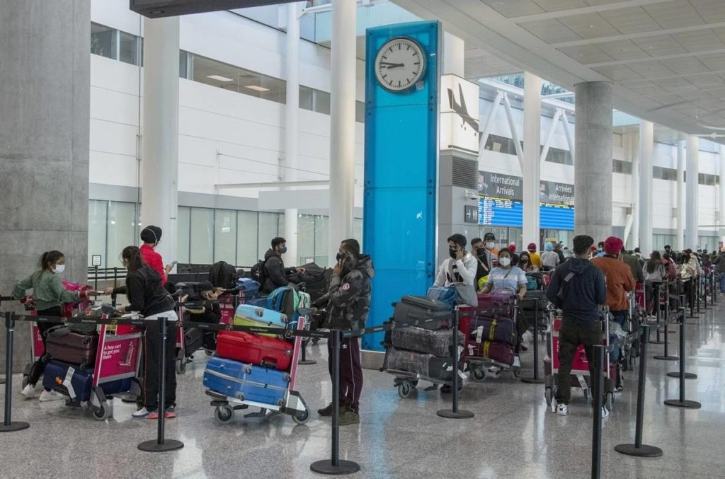 Passengers from New Delhi wait in long lines for transportation to their quarantine hotels at Pearson Airport in Toronto on Friday April 23, 2021. More than 5,000 people tested positive for COVID-19 after flying back to Canada since mandatory quarantine hotels began in late February.THE CANADIAN PRESS/Frank Gunn