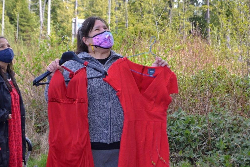 Jennifer Touchie prepares to re-hang red dresses on May 1 after vandals removed the dresses she had originally hung along Highway 4 days before. (Nora O'Malley photo)