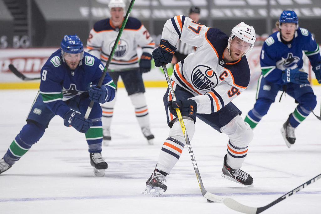 Edmonton Oilers' Connor McDavid (97) stickhandles past Vancouver Canucks' J.T. Miller (9) and Alexander Edler (23), of Sweden, during the first period of an NHL hockey game in Vancouver on Monday, May 3, 2021. THE CANADIAN PRESS/Darryl Dyck