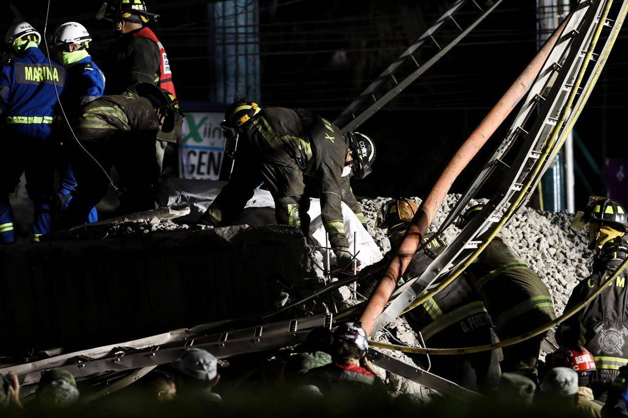 Rescue personnel retrieve bodies from the scene of an accident where subway cars fell after a section of Line 12 of the subway collapsed in Mexico City, Tuesday, May 4, 2021. The section passing over a road in southern Mexico City collapsed Monday night, dropping a subway train, trapping cars and causing at least 50 injuries and several dead, authorities said. (AP Photo/Marco Ugarte)