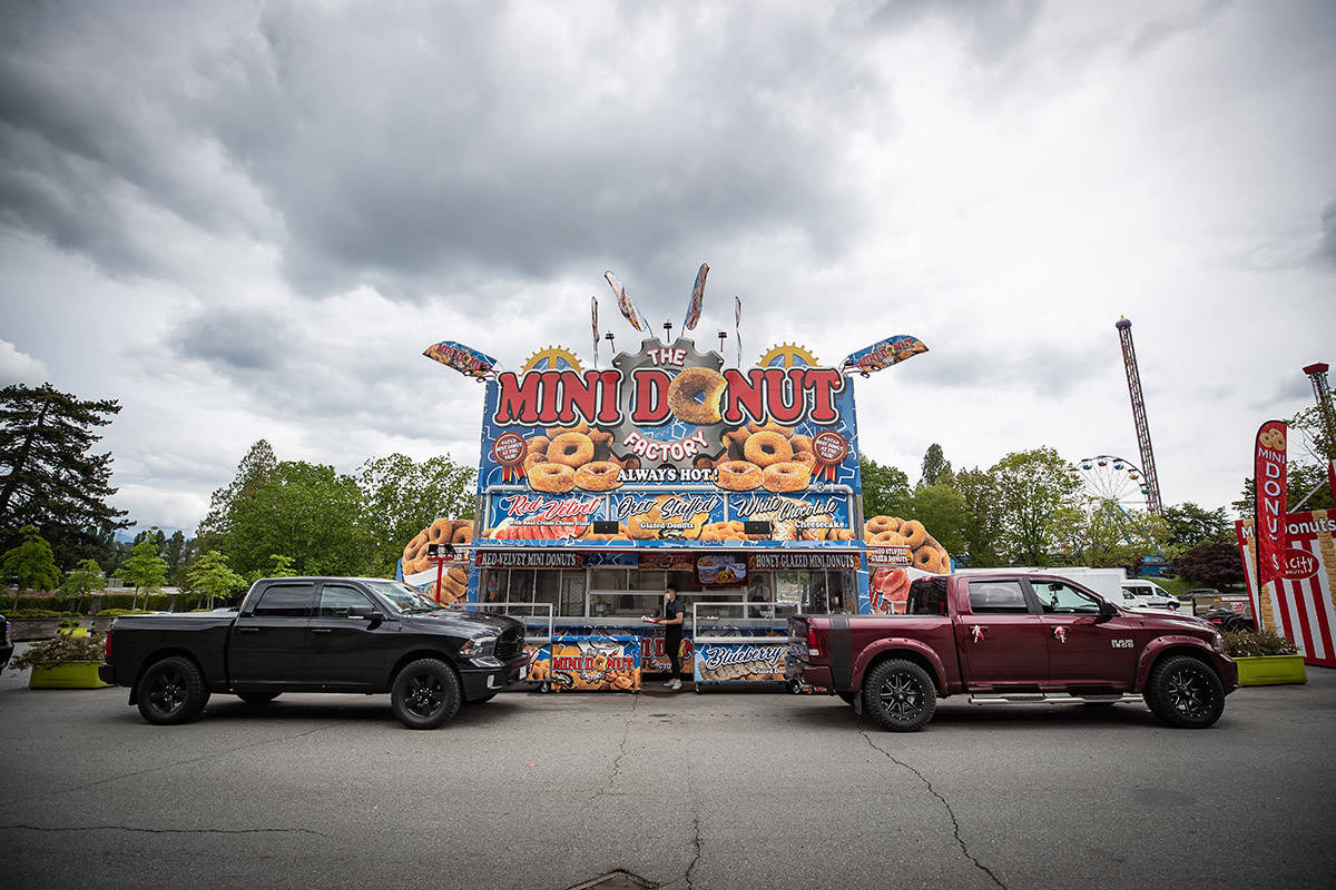 FILE – A vendor waits to serve mini doughnuts to a motorist at a drive-thru event with mini doughnut vendors at the Pacific National Exhibition grounds, in Vancouver, on Sunday, May 24, 2020. The PNE organized the event to help support vendors who will be unable to sell at the fair this year due to the cancellation of the annual event because of COVID-19. THE CANADIAN PRESS/Darryl Dyck
