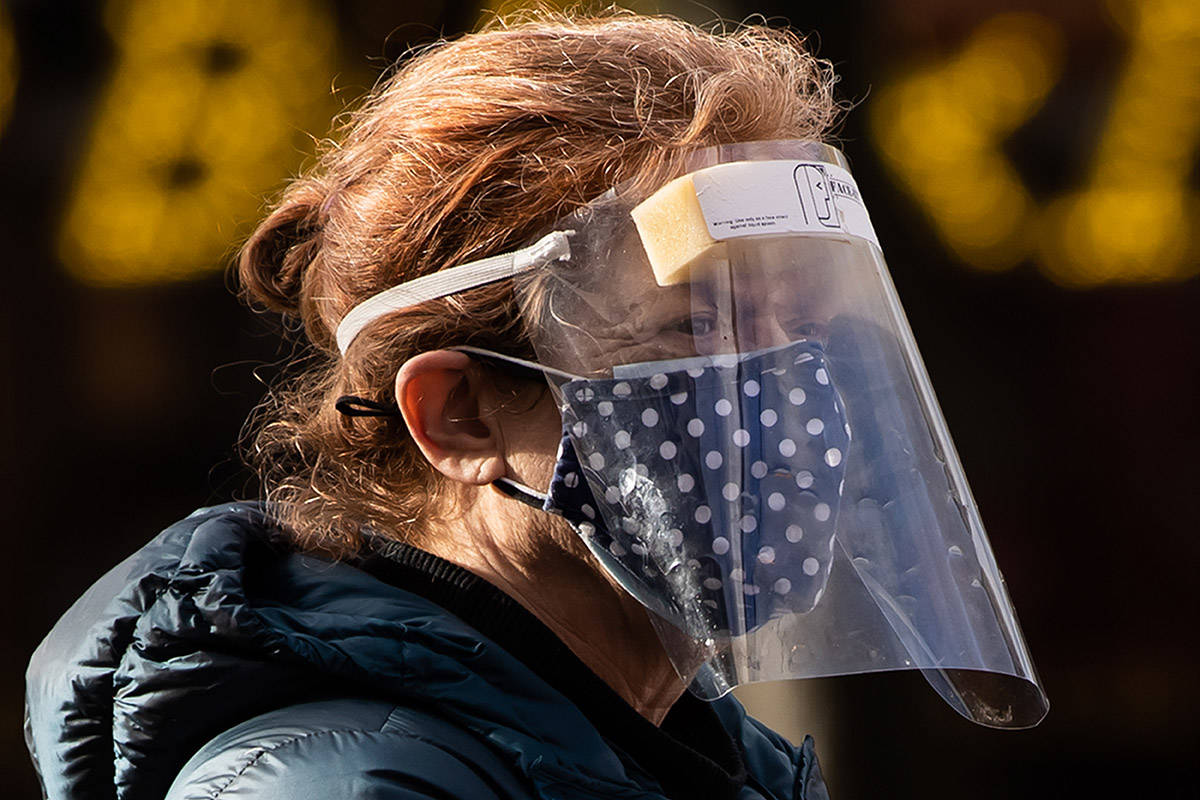 A woman wears a face mask and shield to curb the spread of COVID-19 while walking in North Vancouver, B.C., on Wednesday, January 6, 2021. THE CANADIAN PRESS/Darryl Dyck