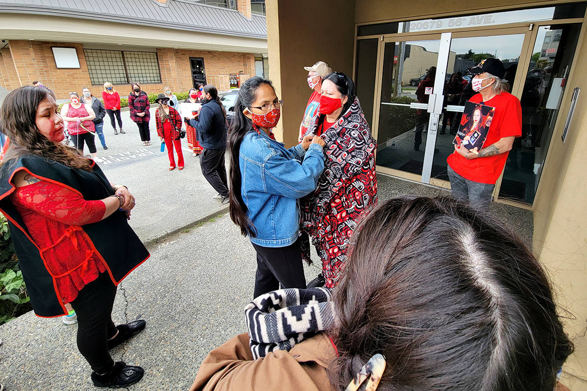 The family of missing woman Kristina Ward was 'blanketed' before about 60 people took part in a Wednesday march through Langley City, marking Red Dress Day, the day to remember missing and murdered Indigenous women. Organizer Laura Sheck-Bell, at left, said it was the first of many marches.(Dan Ferguson/Langley Advance Times)
