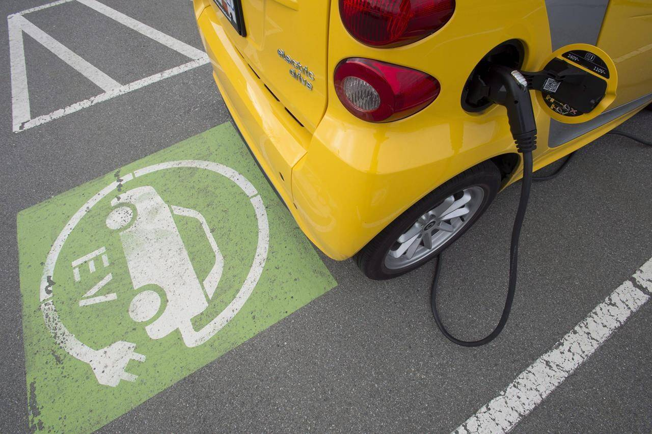An electric car is seen getting charged at parking lot in Tsawwassen, near Vancouver, Friday, April, 6, 2018. Should Canada introduce a national mandate requiring the auto industry make or sell more zero-emission vehicles is a question facing the Liberal government as it's not on the road to meet its own sales targets. THE CANADIAN PRESS/Jonathan Hayward