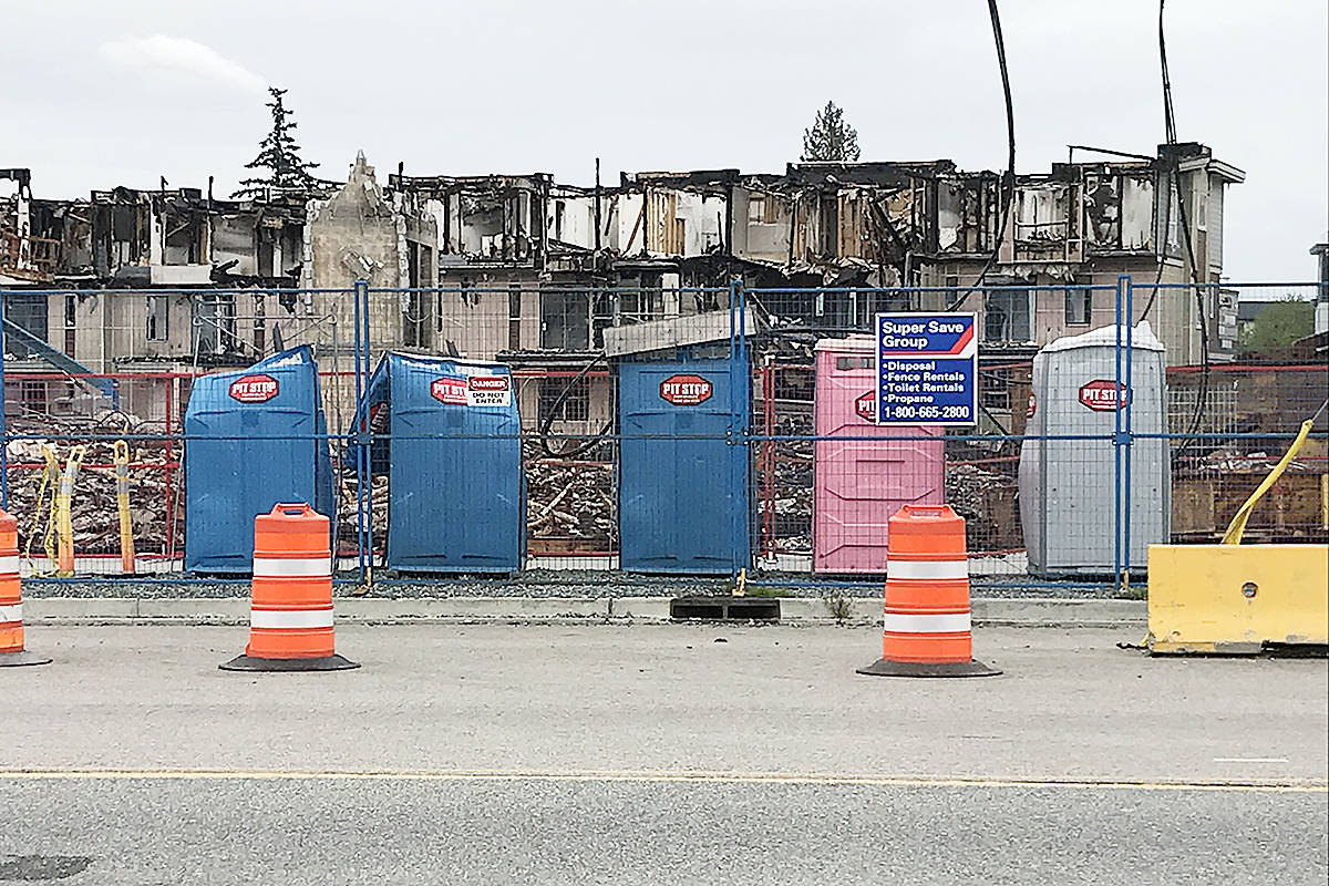 A row of half-melted portable toilets sit in front of the debris at the site of the April 19 fire. Cleanup could start as soon as Monday, May 10. (Matthew Claxton/Langley Advance Times)