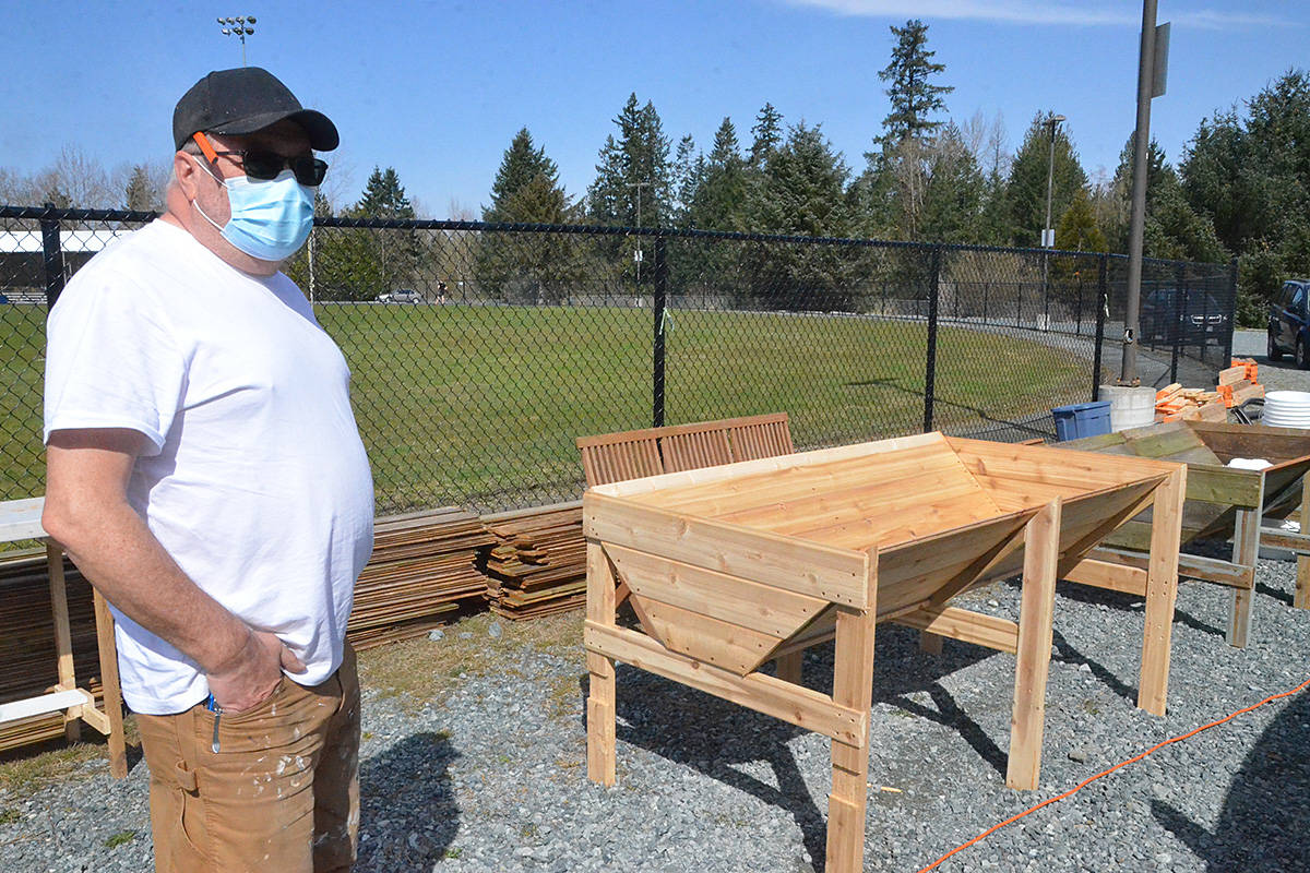 Tim Kreiter shows off the raised garden bed cradles he's been building at the TWU site. (Matthew Claxton/Langley Advance Times)