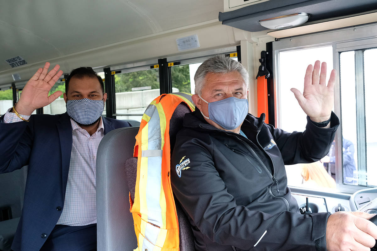 School Board chairperson Ravi Parmar is pumped to be at the front of the province's first electric school bus, driven by Al Kowalko on the West Shore. (Zoe Ducklow/News Staff)