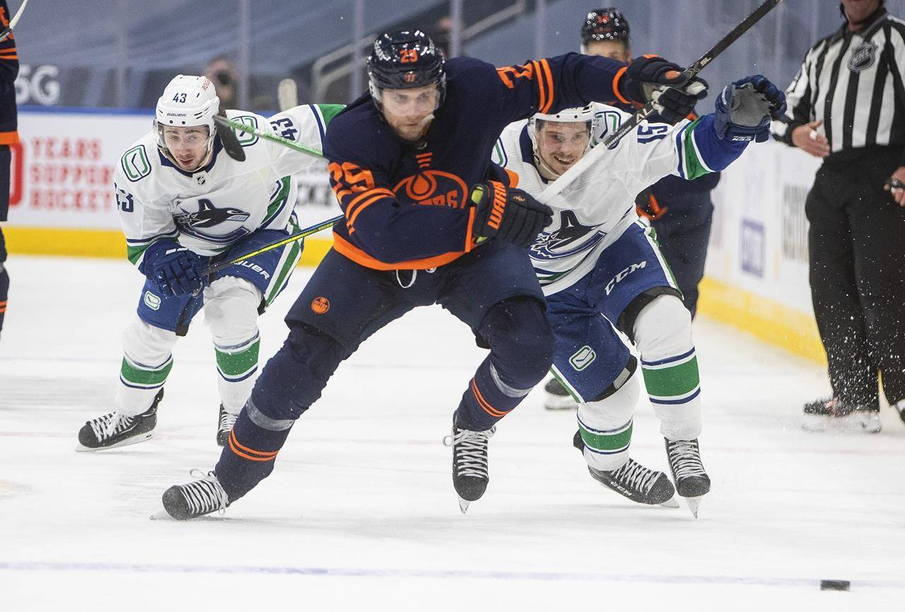Edmonton Oilers' Leon Draisaitl (29) is chased by Vancouver Canucks' Quinn Hughes (43) and Matthew Highmore (15) during second-period NHL action in Edmonton on Thursday, May 6, 2021.THE CANADIAN PRESS/Jason Franson
