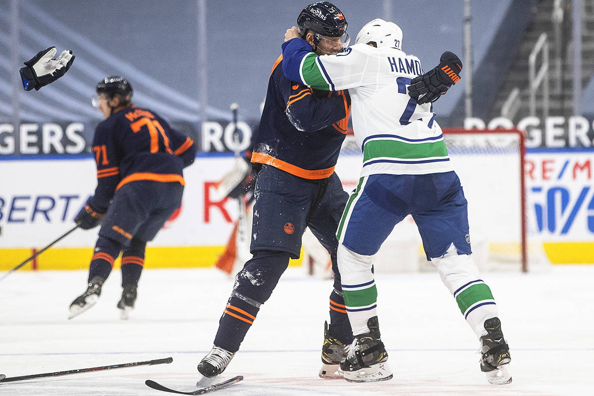 Edmonton Oilers' Alex Chiasson (39) and Vancouver Canucks' Travis Hamonic (27) fight during second period NHL action in Edmonton on Thursday, May 6, 2021.THE CANADIAN PRESS/Jason Franson