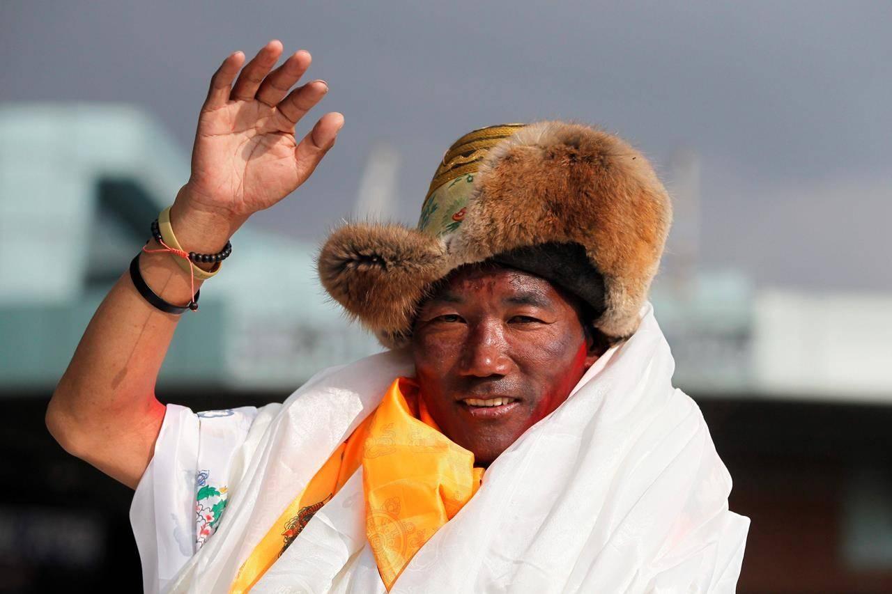Nepalese veteran Sherpa guide, Kami Rita waves as he arrives in Kathmandu, Nepal. (AP Photo/Niranjan Shrestha)