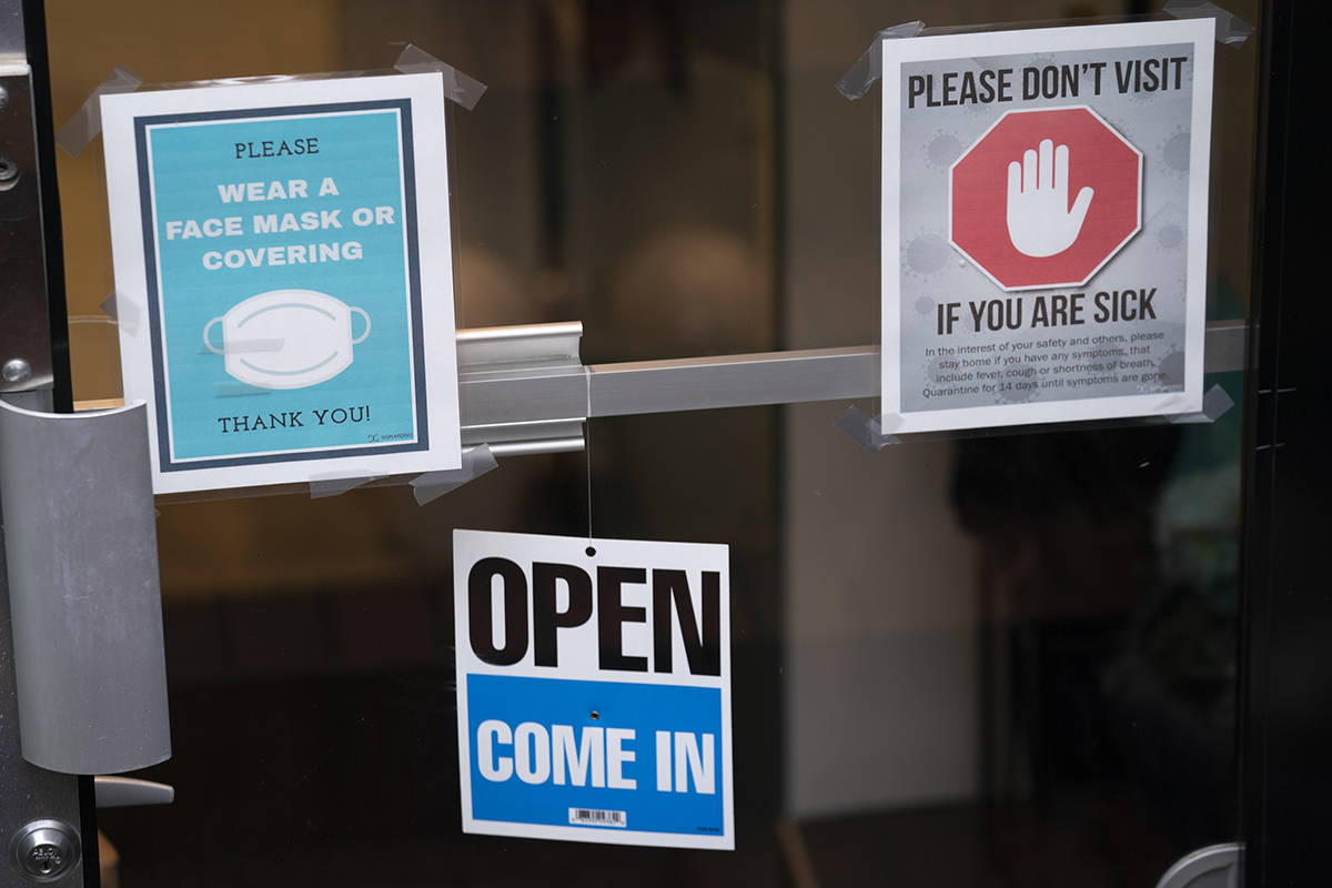 A sign indicating face coverings are required by the establishment is pictured on the front door of a business in Vancouver, B.C., Friday, April 9, 2021. COVID-19 cases have been on a steady increase in the province of British Columbia over the past week. THE CANADIAN PRESS/Jonathan Hayward A sign indicating face coverings are required by the establishment is pictured on the front door of a business in Vancouver, B.C., Friday, April 9, 2021. COVID-19 cases have been on a steady increase in the province of British Columbia over the past week. THE CANADIAN PRESS/Jonathan Hayward