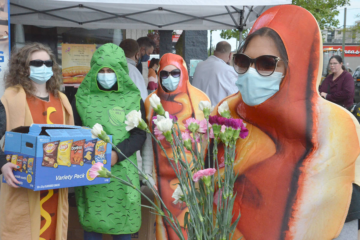 Melissa Vandergenderen, Sandeep Chahal, Niole Garfias and Sheela Veloo had fun attracting passersby to the hot dog sale downtown Friday, May 7, 2021. The event raised funds for the Langley Seniors Resource Society Adult Day Program. (Heather Colpitts/Langley Advance Times)