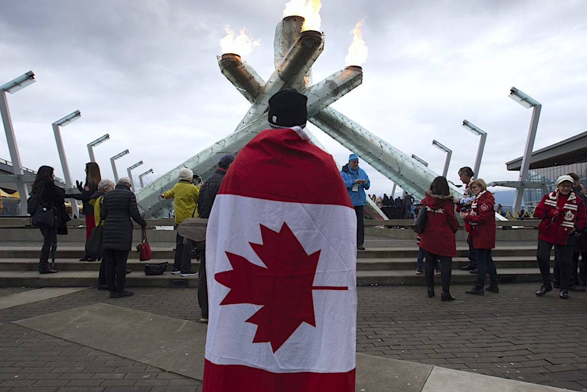A spectator looks on as the Olympic Caldron is relit in downtown Vancouver, Wednesday, February 12, 2020. THE CANADIAN PRESS/Jonathan Hayward