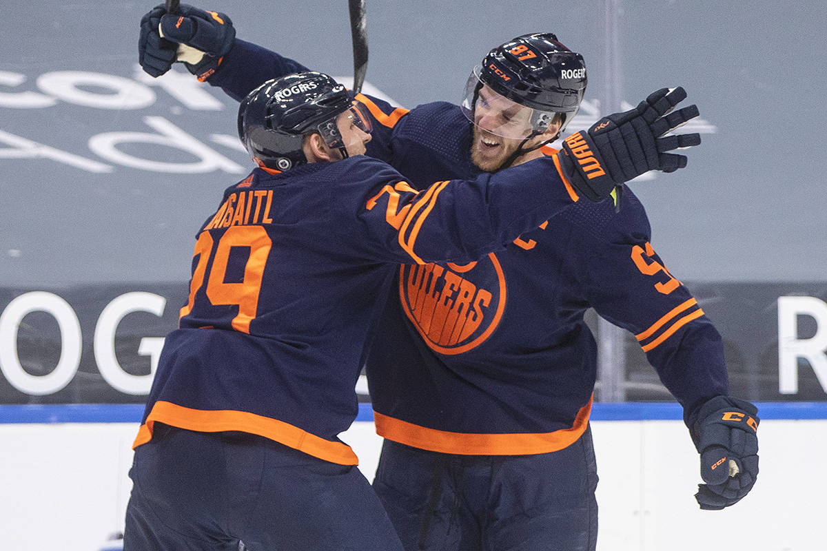 Edmonton Oilers' Connor McDavid (97) celebrates his 100th point this season with Leon Draisaitl (29) against the Vancouver Canucks during second period NHL action in Edmonton on Saturday, May 8, 2021.THE CANADIAN PRESS/Jason Franson