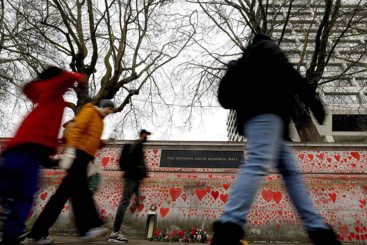 People pass the red hearts on the COVID-19 Memorial Wall mourning those who have died, opposite the Houses of Parliament on the Embankment in London, Wednesday, April 7, 2021. On May 3, the British government announced that only one person had died of COVID-19 in the previous 24 hours. THE CANADIAN PRESS/AP-Kirsty Wigglesworth