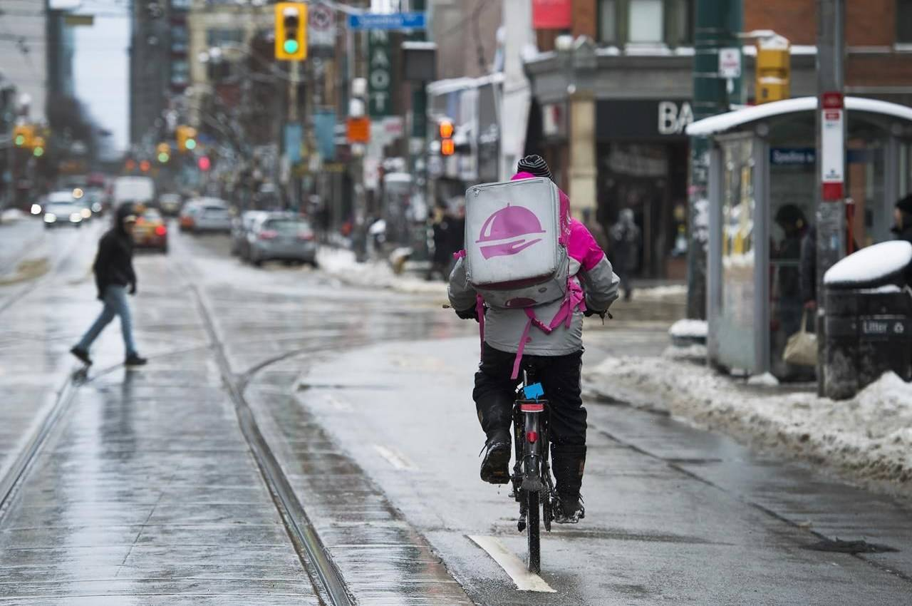 A Foodora courier is pictured as they pick up an order for delivery from a restaurant in Toronto, Thursday, Feb. 27, 2020. THE CANADIAN PRESS/Nathan Denette