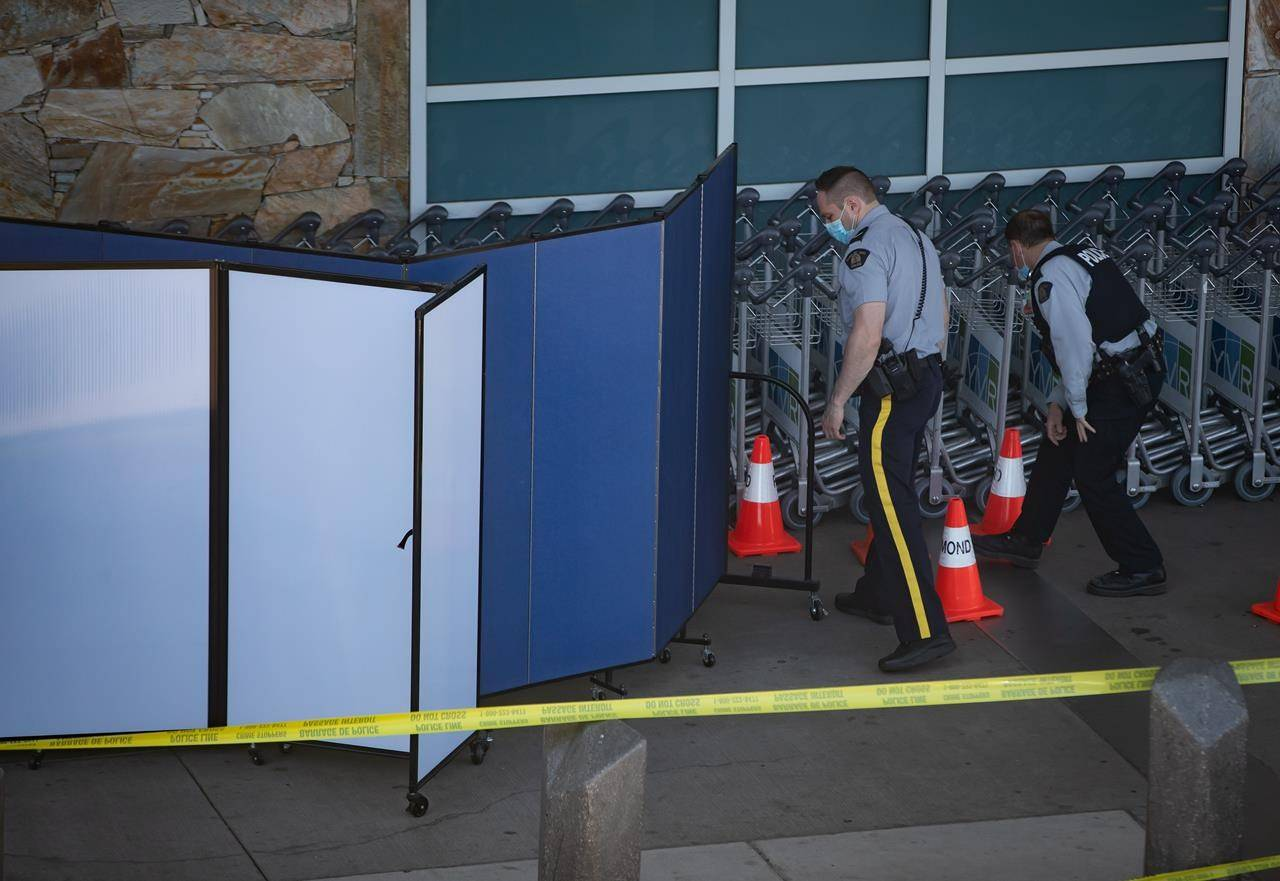 RCMP officers search around rows of luggage carts as screens block off an area of the sidewalk after a shooting outside the international departures terminal at Vancouver International Airport, in Richmond, B.C., Sunday, May 9, 2021. THE CANADIAN PRESS/Darryl Dyck