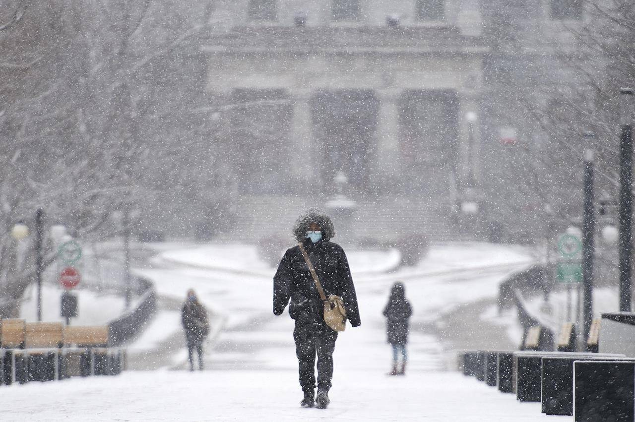 A person wears a face mask as they walk through McGill University during light snowfall in Montreal, Sunday, December 20, 2020 as the COVID-19 pandemic continues in Canada and around the world. THE CANADIAN PRESS/Graham Hughes