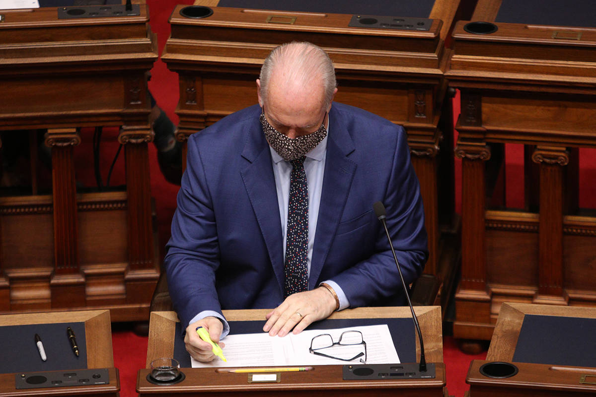 British Columbia Premier John Horgan highlights a paragraph as Finance Minister Selina Robinson tables the budget in a speech in the legislative assembly at the provincial legislature in Victoria, Tuesday, April 20, 2021. THE CANADIAN PRESS/Chad Hipolito