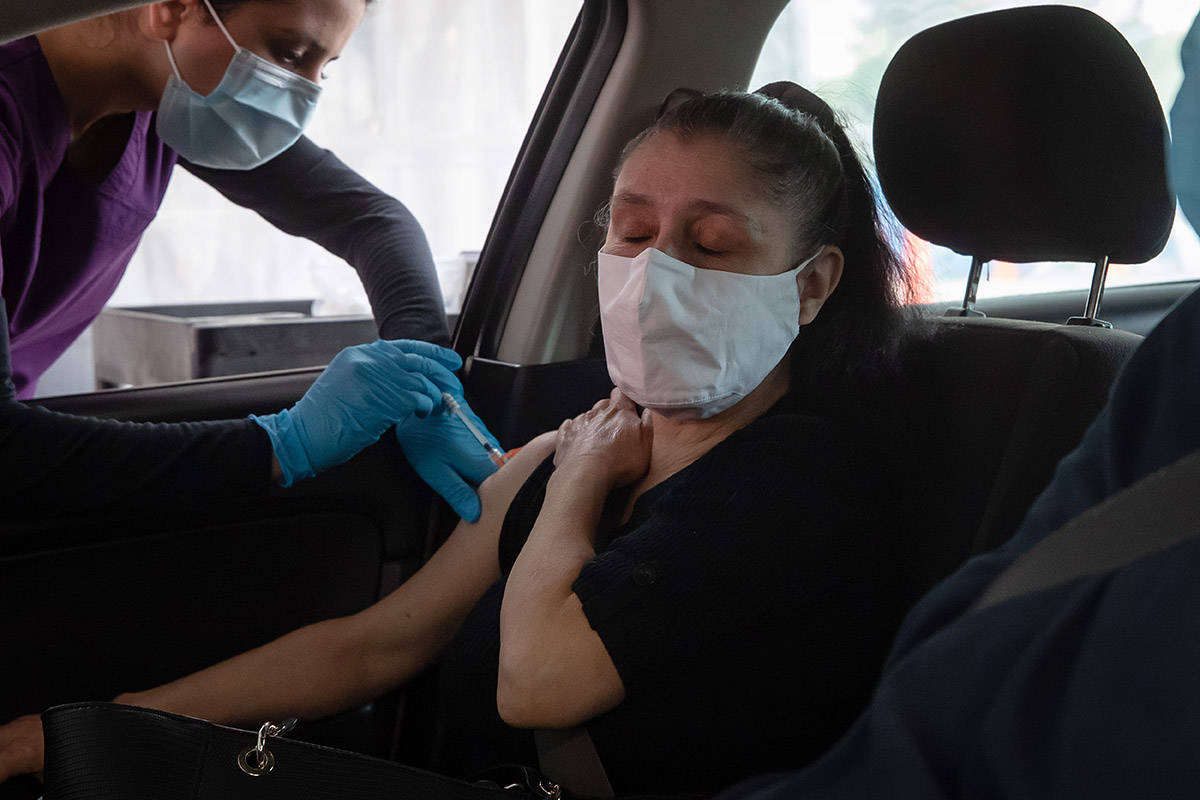 Nurse Gurinder Rai, left, administers the Moderna COVID-19 vaccine to Maria Yule at a Fraser Health drive-thru vaccination site, in Coquitlam, B.C., on Wednesday, May 5, 2021. The site is open for vaccinations 11 hours per day to those who have pre-booked an appointment. THE CANADIAN PRESS/Darryl Dyck