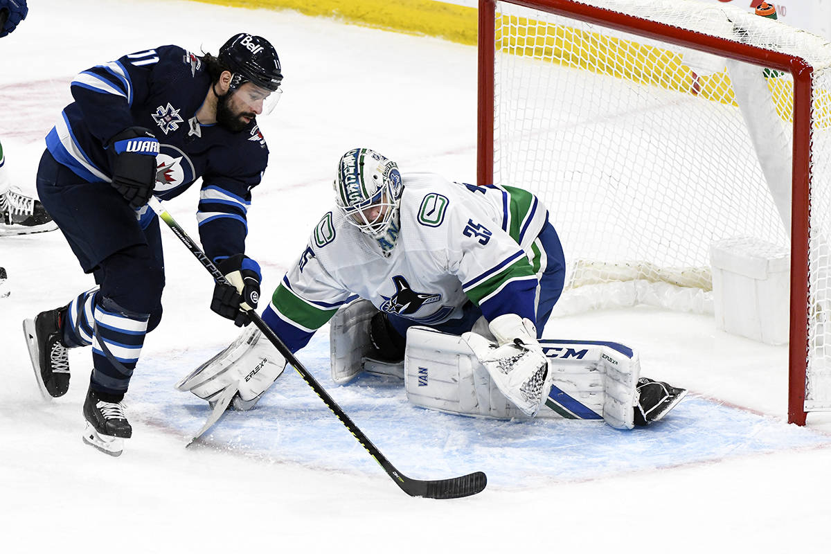 Vancouver Canucks goaltender Thatcher Demko (35) makes a save on Winnipeg Jets' Nate Thompson (11) during second period NHL action in Winnipeg, Monday, May 10, 2021. THE CANADIAN PRESS/Fred Greenslade