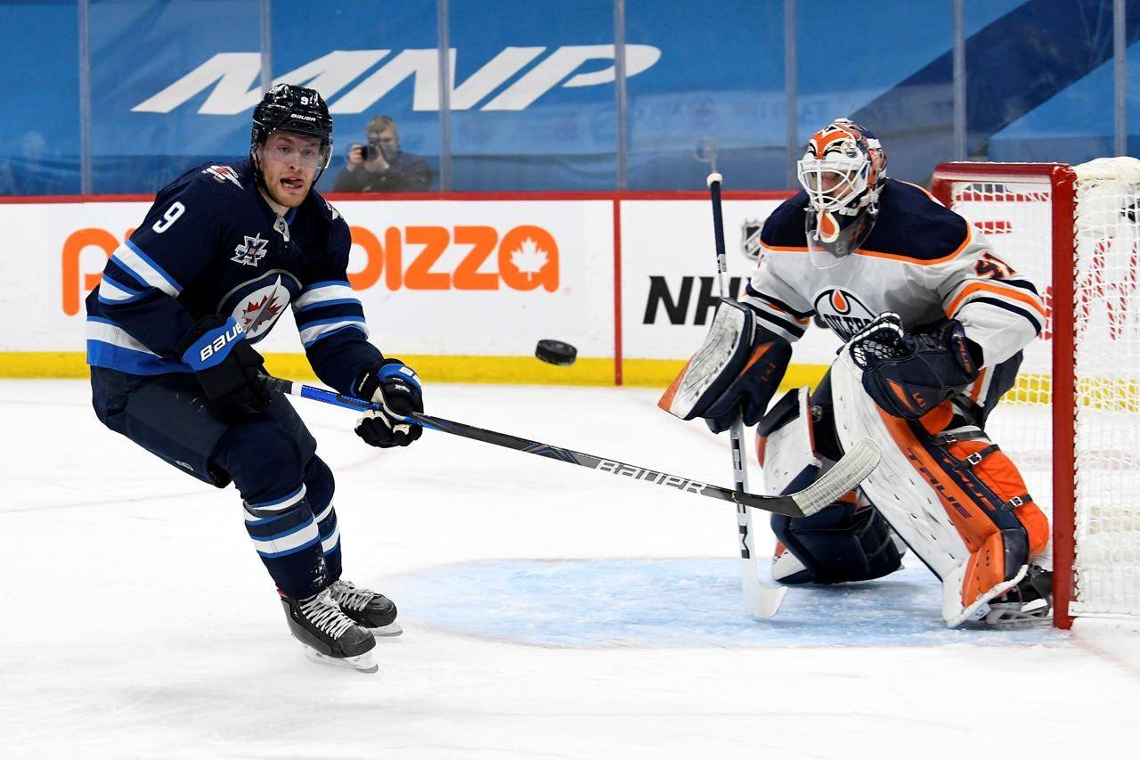 Winnipeg Jets' Andrew Copp (9) and Edmonton Oilers goaltender Mike Smith (41) watch an incoming shot during second period NHL action in Winnipeg, Monday, April 26, 2021. THE CANADIAN PRESS/Fred Greenslade