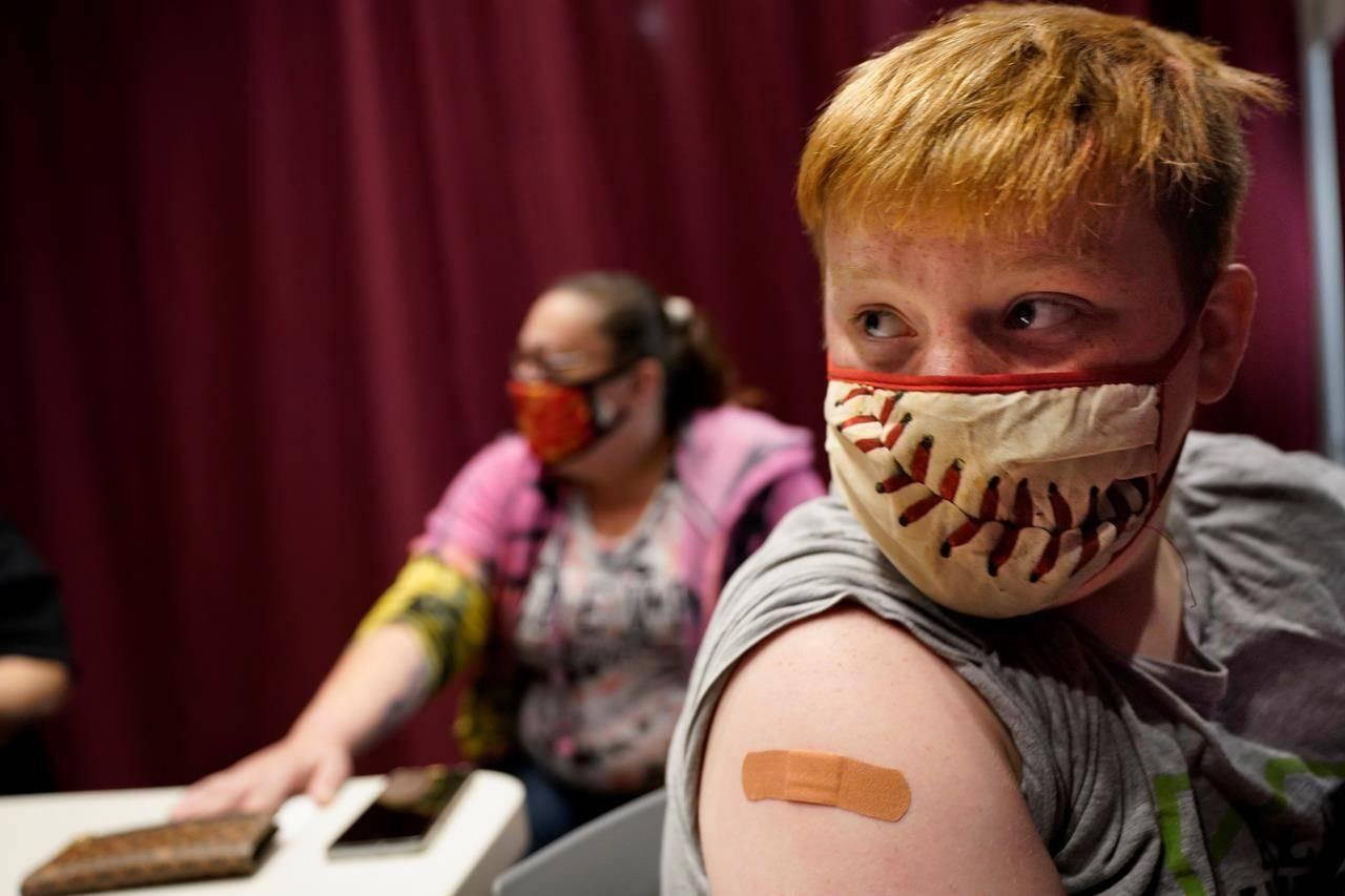 Jacob Conary, 15, listens to advice from a medical assistant after receiving his first shot of the COVID-19 vaccination, Wednesday, May 12, 2021, in Auburn, Maine. (AP/Robert F. Bukaty)