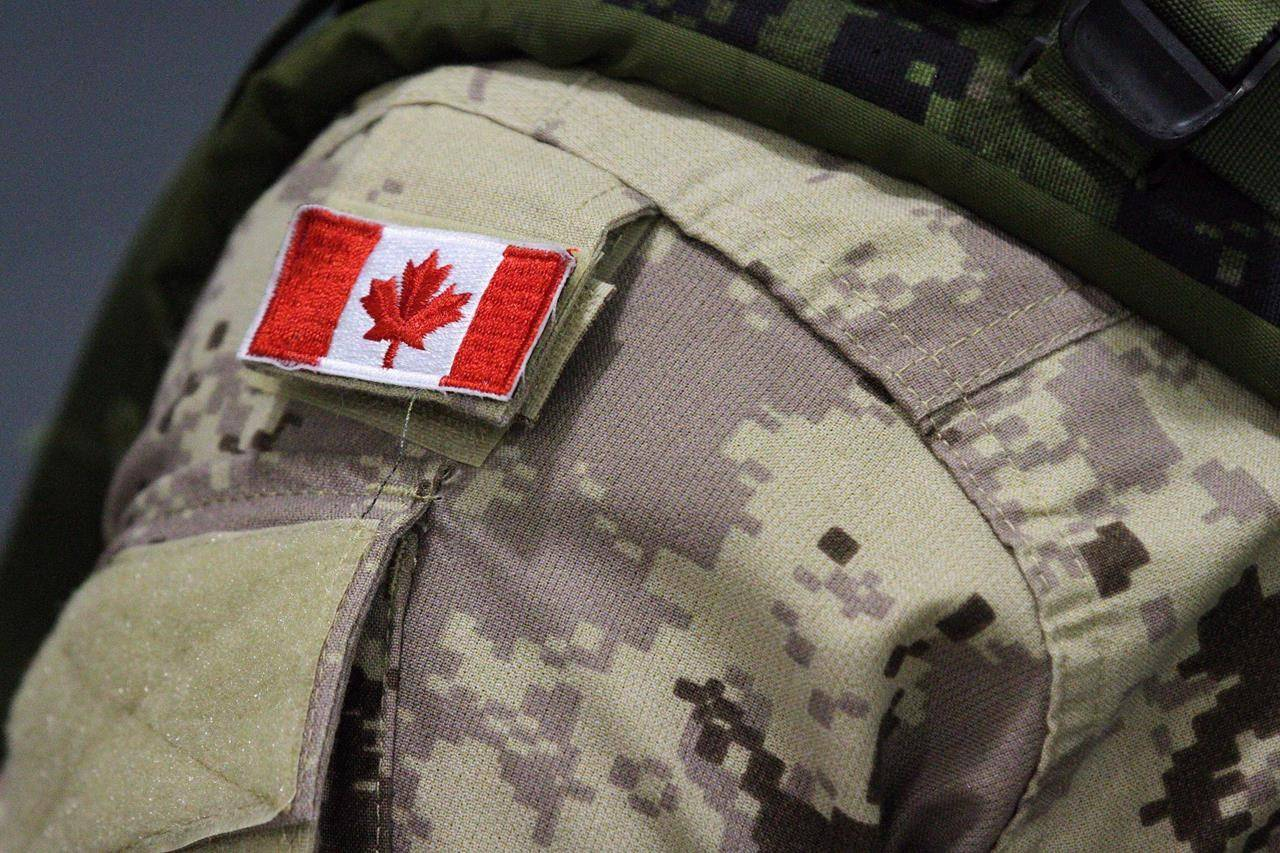 A Canadian flag patch is shown on a soldier's shoulder in Trenton, Ont., on Thursday, Oct. 16, 2014. The Canadian Forces says it has charged one of its members in the death of an army reservist from British Columbia during a training exercise at a military base in Alberta last year. THE CANADIAN PRESS/Lars Hagberg