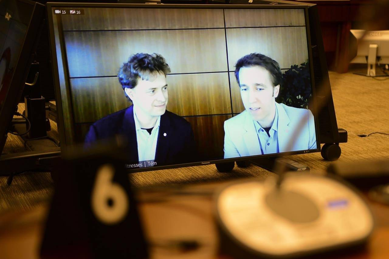 Marc Kielburger, screen left, and Craig Kielburger, screen right, appear as witnesses via video conference during a House of Commons finance committee in the Wellington Building in Ottawa on Tuesday, July 28, 2020. The committee is looking into Government Spending, WE Charity and the Canada Student Service Grant. THE CANADIAN PRESS/Sean Kilpatrick