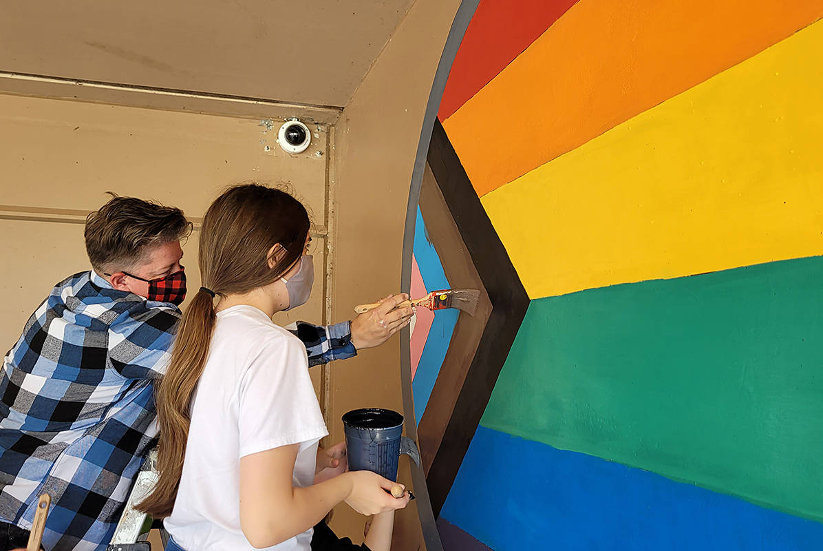 Lorna Seip touches up the mural on the wall at MRSS, working with students from the Rainbow Club. (Neil Corbett/The News)