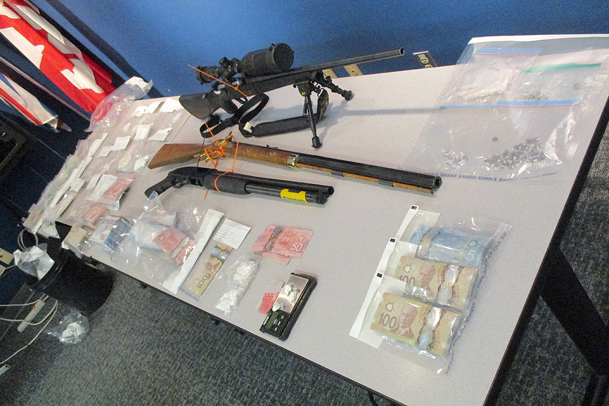Three guns, cash, and drugs seized in raids in Langley and Vernon targeting a suspected dial-a-dope ring. (Langley RCMP/Special to the Langley Advance Times)