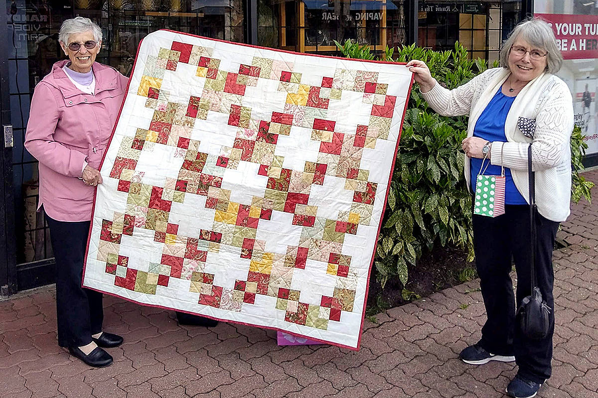 "Langley Quilters Guild helped honour two long-time members of the Langley Memorial Hospital Auxiliary, including Pat Walker (left), with ""beautiful quilts"" to express appreciation for their years of service to the non-profit. Her quilt was presented by Nuala Adderley (right), the guild vice-president. (Special to Langley Advance Times)"