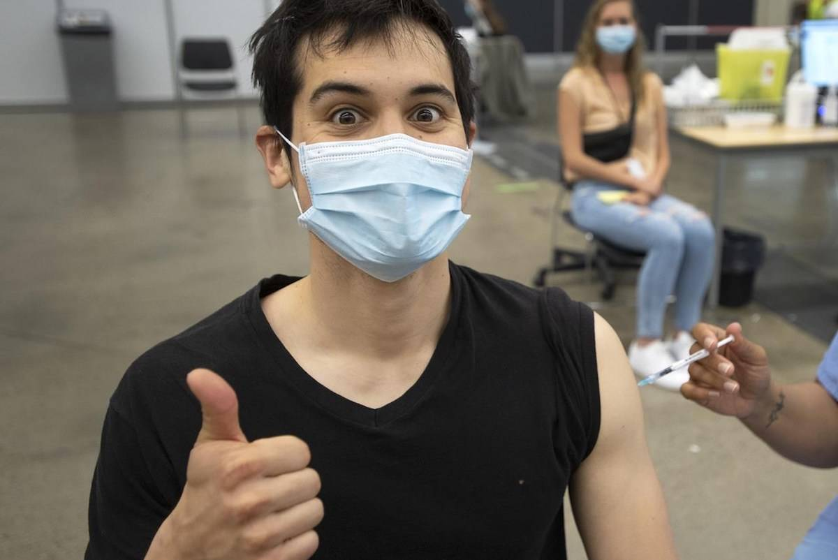 Adam Feller reacts as he gets his Pfizer-BioNTech shot at a COVID-19 vaccination clinic on Thursday, May 13, 2021, in Montreal. THE CANADIAN PRESS/Ryan Remiorz