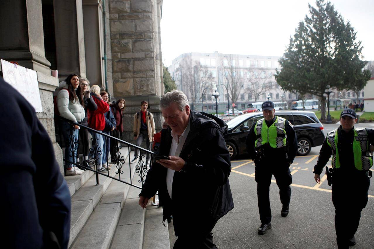 Then-minister Rich Coleman, escorted by Victoria Police, makes his way to the east wing amid a protest blocking the legislature entrances before the throne speech in Victoria, B.C., Tuesday, Feb. 11, 2020. THE CANADIAN PRESS/Chad Hipolito