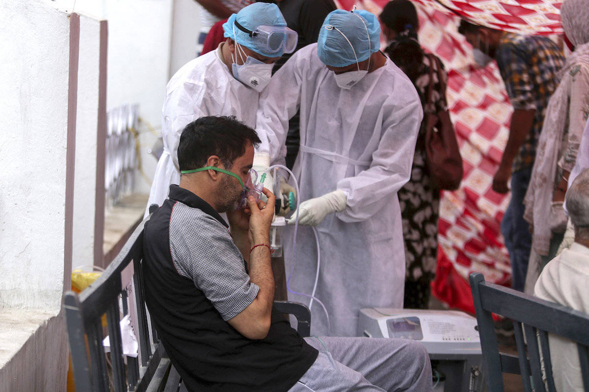 A COVID-19 patient receives oxygen outside a hospital in Jammu, India, Wednesday, May 12, 2021. (AP/Channi Anand)