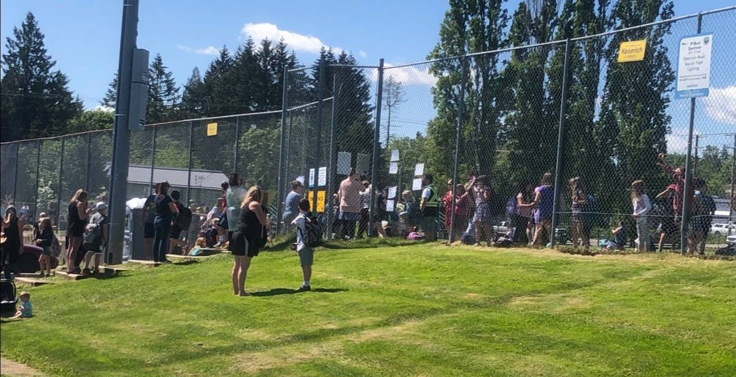 Ecole Mount Prevost Elementary parents are in line to pick up their children after a police incident nearby saw students evacuated to the Sherman Road soccer fields. (Kevin Rothbauer/Citizen)