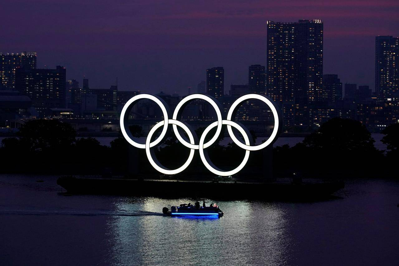 The Olympic rings float in the water at sunset in the Odaiba section of Tokyo, Wednesday, June 3, 2020. THE CANADIAN PRESS/AP